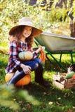 Gelukkige het meisje van het landbouwersjonge geitje het plukken de herfst plantaardige oogst in de tuin stock foto