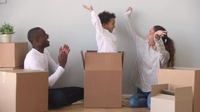 Gelukkige het mengen-behoren tot een bepaald rasfamilie die pret uitpakkende dozen bij het bewegen van dag hebben stock videobeelden
