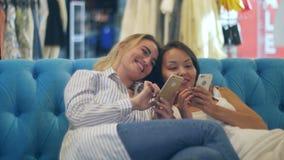 Gelukkige het winkelen smartphone van het vrouwengebruik en lachzitting in wandelgalerij stock footage