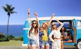 Gelukkige hippievrienden bij minivan auto op strand Stock Afbeeldingen