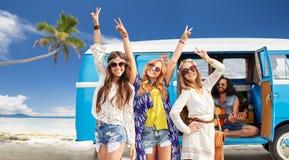 Gelukkige hippievrienden bij minivan auto op strand Royalty-vrije Stock Afbeeldingen