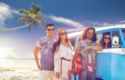 Gelukkige hippievrienden bij minivan auto op strand Stock Foto's
