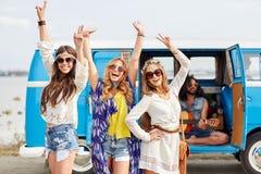 Gelukkige hippievrienden die pret over minivan auto hebben Stock Afbeeldingen