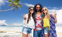 Gelukkige hippievrienden die vrede op de zomerstrand tonen Stock Foto