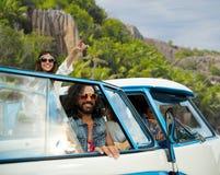 Gelukkige hippievrienden in minivan auto op eiland Stock Foto