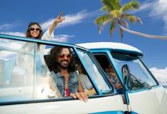 Gelukkige hippievrienden in minivan auto op strand Royalty-vrije Stock Afbeeldingen