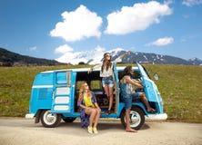 Gelukkige hippievrienden in minivan auto over bergen Royalty-vrije Stock Foto's
