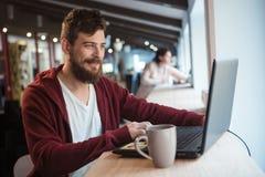 Gelukkige hipster die in het bureau werken die laptop met behulp van stock fotografie
