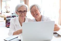 Gelukkige hogere Aziatische en vrouw twee, zusters of vrienden die gebruikend laptop computer die samen thuis, bejaarde mensen gl stock afbeeldingen