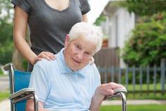 Gelukkige hogere dame in rolstoel met caregiver royalty-vrije stock foto's