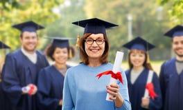 Gelukkige hogere gediplomeerde studentenvrouw met diploma stock foto