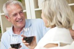 Gelukkige Hogere het Drinken van het Paar Wijn thuis Stock Foto's