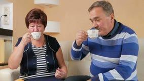 Gelukkige hogere man en vrouw die thuis meer dan een kop van koffie spreken Echtgenoot en vrouw in een mooi huis om te bespreken stock footage