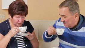 Gelukkige hogere man en vrouw die thuis meer dan een kop van koffie spreken Echtgenoot en vrouw in een mooi huis om te bespreken stock video