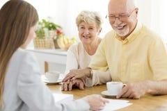 Gelukkige hogere mens en zijn vrouw die met financiële adviseur converseren royalty-vrije stock afbeelding