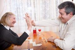 Gelukkige hogere mensen in speel de dominospel van het pensioneringshuis Stock Afbeelding
