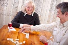 Gelukkige hogere mensen in speel de dominospel van het pensioneringshuis Royalty-vrije Stock Fotografie