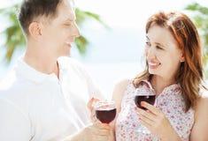 Gelukkige hogere midden-leeftijdspaar het drinken wijn op overzeese strandachtergrond - het concept van de zomermensen stock afbeeldingen