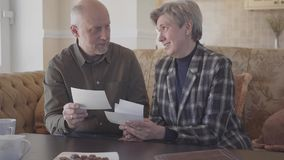 Gelukkige hogere oude paar, man en vrouwenzitting in de bank, het spreken, het lachen en het letten op foto's, die zich voorbij h stock video