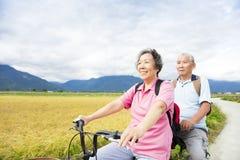 Gelukkige Hogere Paar Berijdende Fiets bij de landweg stock afbeeldingen