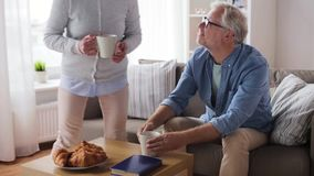 Gelukkige hogere paar het drinken koffie thuis stock videobeelden
