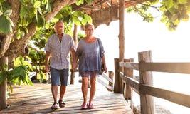 Gelukkige hogere paar het lopen holdingshand bij Koh Phangan-strandpromenade - Actieve bejaarden en het concept van de reislevens stock foto's
