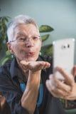 Gelukkige hogere vrouw die kus over skype verzenden Stock Afbeeldingen