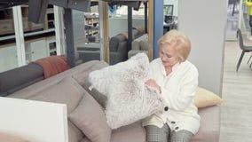 Gelukkige hogere vrouw die kussens voor haar woonkamer kiezen bij meubilairopslag stock footage
