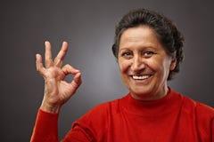 Gelukkige hogere vrouw die o.k. teken maakt stock afbeeldingen