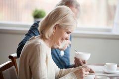Gelukkige hogere vrouw die ontbijt met oude echtgenoot hebben thuis stock afbeeldingen