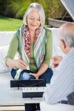 Gelukkige Hogere Vrouw die Rummy With Man spelen royalty-vrije stock foto's