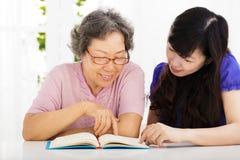 Gelukkige hogere vrouw en dochter die een boek lezen royalty-vrije stock afbeelding