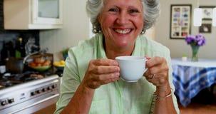 Gelukkige hogere vrouw het drinken koffie in keuken 4k stock video