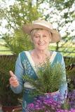 Gelukkige hogere vrouw met bloemen stock afbeeldingen