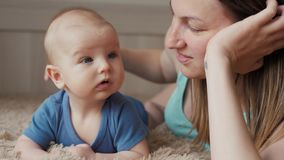 Gelukkige houdende van familie De jonge moeder speelt met haar babymeisje in de slaapkamer Het mamma en het kind hebben pret op h stock videobeelden