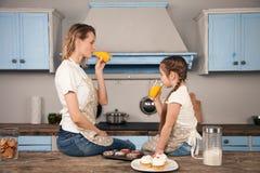 Gelukkige houdende van familie in de keuken Moeder en kind het dochtermeisje eet koekjes die zij met een sinaasappel hebben gemaa royalty-vrije stock foto
