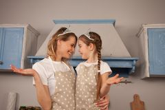 Gelukkige houdende van familie in de keuken Moeder en kind het dochtermeisje heeft pret dragend kronen, bekijkend elkaar royalty-vrije stock foto