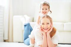 Gelukkige houdende van familie moeder en kind spelen die op de vloer liggen Stock Fotografie
