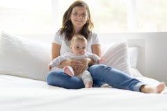 Gelukkige houdende van familie moeder het spelen met haar baby in de slaapkamer Stock Afbeeldingen