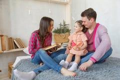 Gelukkige houdende van familie Vrij jonge moeder die een boek lezen aan haar dochter stock afbeelding