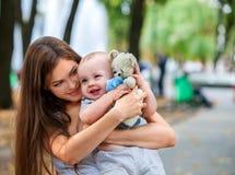 Gelukkige houdende van moeder en haar baby in openlucht met teady beer Royalty-vrije Stock Foto