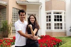 Gelukkige huiseigenaars infront van nieuw huis Stock Foto
