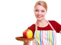 Gelukkige huisvrouw of chef-kok in geïsoleerde keukenschort die appel tonen royalty-vrije stock fotografie
