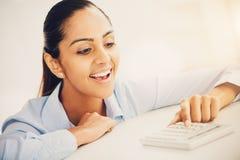 Gelukkige Indische bedrijfsvrouw die calculator gebruiken Stock Foto