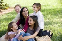 Gelukkige interracial familie van vijf die van een picknick genieten Royalty-vrije Stock Afbeelding