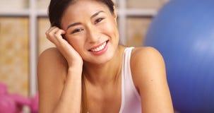Gelukkige Japanse vrouw die op matte yoga liggen stock afbeeldingen