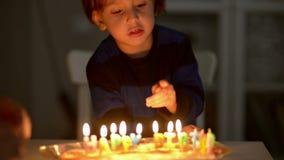 Gelukkige jong geitje blazende kaarsen bij zijn verjaardag stock videobeelden