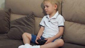 Gelukkige jong geitje het spelen videospelletjes en het zitten op een bank stock video