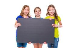 Gelukkige jong geitjemeisjes die zwarte raad houden copyspace Stock Fotografie
