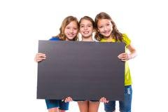 Gelukkige jong geitjemeisjes die zwarte raad houden copyspace Stock Foto's